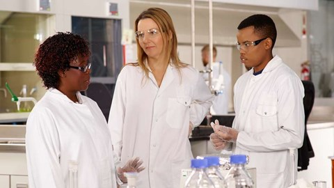 Three scientists talking in a lab in Cape Town, South Africa